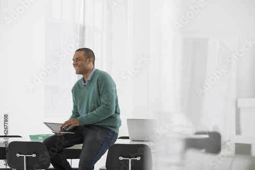 Business. A Man Leaning On A Desk Holding A Digital Tablet.