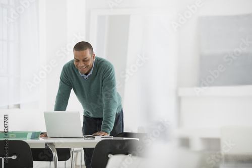 Business. A Man Standing Over A Desk, Leaning Down To Use A Laptop Computer.