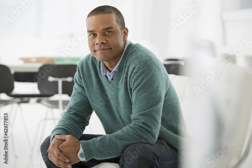 Business. A Man Sitting, Hands Clasped In A Relaxed Confident Pose.