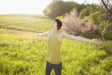 Young Woman Standing In Grassy Field In Spring.