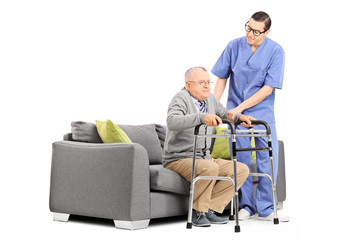 Male nurse helping an elderly gentleman to stand up