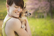 A Young Woman In A Grassy Field In Spring. Holding A Small Chihuahua Dog In Her Arms. A Pet.