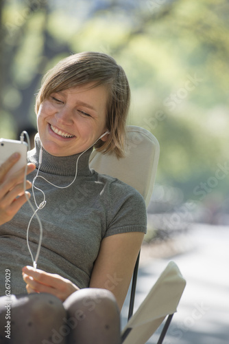 City Life. A Woman Sitting In A Camping Chair In The Park, Listening To Music Wearing Headphones.