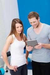 fitness-trainer bespricht trainingsplan mit kundin