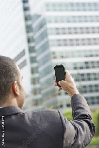 City. A Man In A Business Suit Holding His Smart Phone At Arms Length.