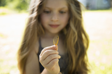 A Young Girl With Long Blonde, Holding A Delicate Lacey Patterned Discarded Butterfly Wing.