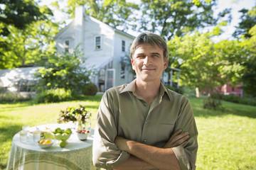 On The Farm. A Man In A Farmhouse Garden, Beside A Round Table With Fresh Lemonade Drinks.
