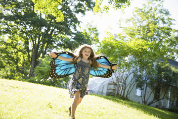 A Child Running Across The Lawn In Front Of A Farmhouse, Wearing Large Irridescent Blue Butterfly Wings And With Her Arms Outstretched.