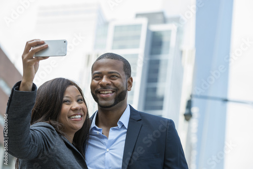 Summer. A Couple Taking A Selfy, A Woman Holding Out A Smart Phone And Taking Their Picture.