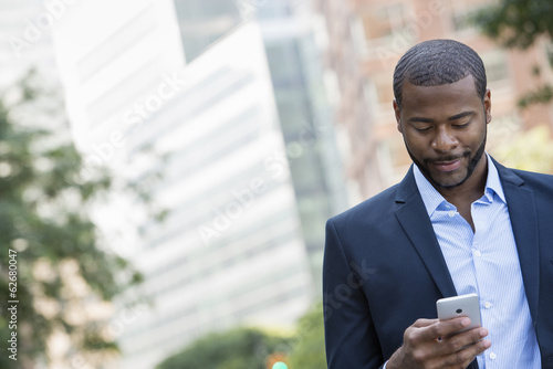 Summer. A Man In A Blue Jacket And Open Collared Shirt Using A Smart Phone.