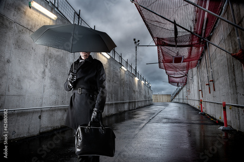 Businessman holding black umbrella on rainy day