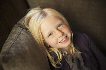 A Girl Sitting On A Couch, Smiling At The Camera.