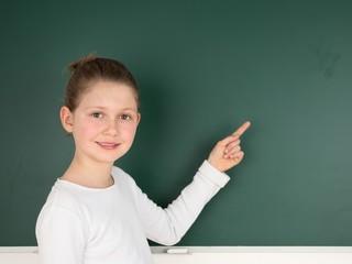 Schülerin zeigt die Tafel im Klassenzimmer