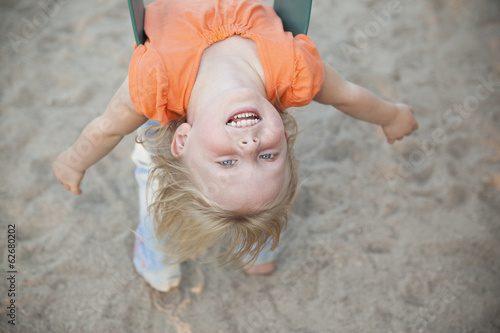 A Child Playing Outdoors. A Girl Hanging Upside Down On A Swing.
