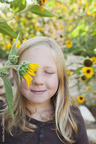 A Child Standing In A Flower Garden. A Girl With Her Eyes Closed With Sun Flower In Front Of Her Eye.
