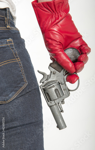 Woman wearing red leather glove holding a gun
