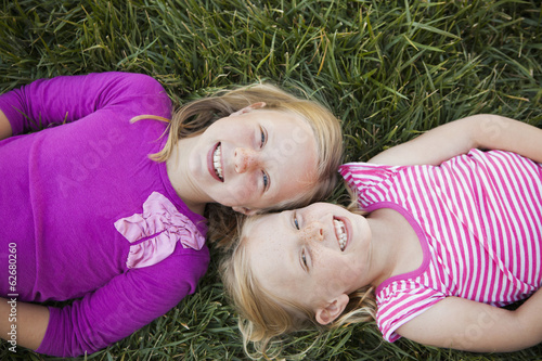A Portrait Of Two Sisters Smiling. View From Above, Of Two Girls Lying On Their Backs On The Grass, Heads Together.