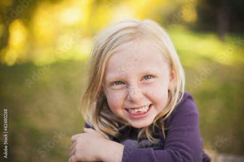 A Girl Sitting On The Grass, Smiling A Big Toothy Smile. Close Up.