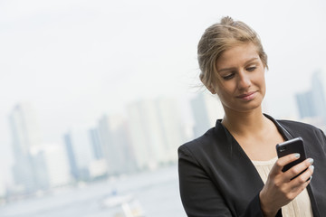 A Young Blonde Businesswoman On A New York City Street. Wearing A Black Jacket. Using A Smart Phone.