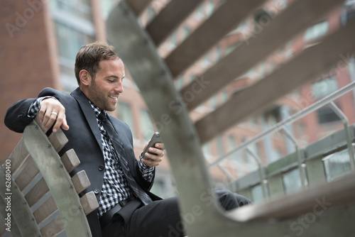 Business People. A Man In A Suit, Sitting On A Bench.