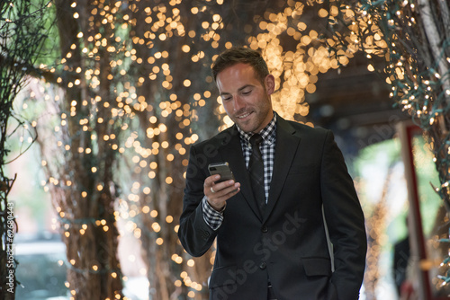 Business People. A Man Checking His Phone, Walking Under A Pergola Lit With Fairy Lights.