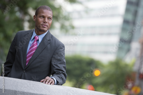 A Young Man In A Business Suit With A Blue Shirt And Red Tie. On A City Street.
