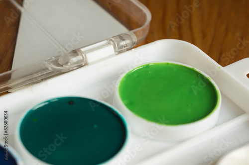 Water color paints of green and emerald color close up