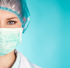 Close-up of woman doctor in surgical mask and cap