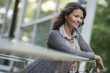 Business People Outdoors. A Businesswoman In A Light Grey Jacket, Leaning On A Railing Smiling. Relaxing.