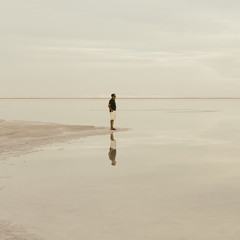 A Man Standing At The Edge Of The Flooded Bonneville Salt Flats At Dusk.