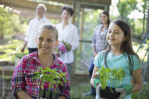 Organic Farm. Summer Party. Two Girls Sitting Holding Young Plants, With A Mature Couple And A Young Woman Looking On.