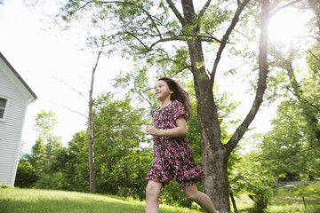 A Young Girl In A Patterned Summer Dress, Running Across The Grass Under The Shade Of Trees In A Farmhouse Garden.