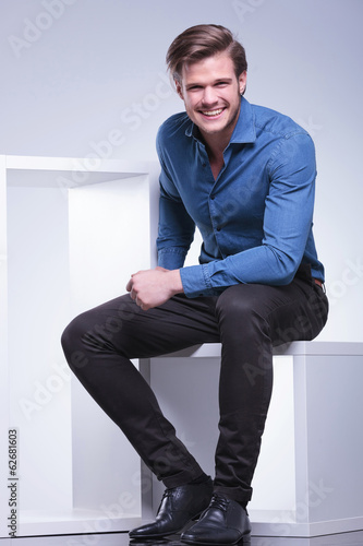 laughing young casual man is sitting in studio