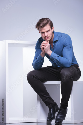 thoughtful young casual man is sitting