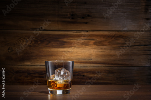 Foto op Plexiglas Alcohol glass of whiskey with ice on a wooden background