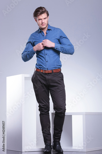 smiling casual young man buttoning his shirt