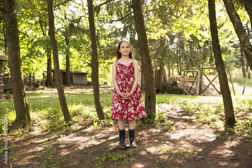 A Girl In A Summer Dress Standing In A Grove Of Trees.