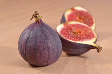 Fresh figs halved on wooden board