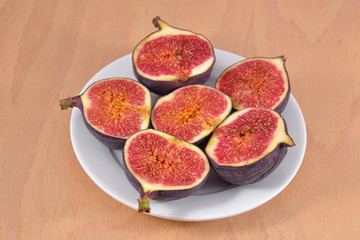 Fresh figs on platе on wooden board
