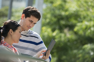 Summer. Business People. A Man And Woman Using A Digital Tablet, Keeping In Touch.