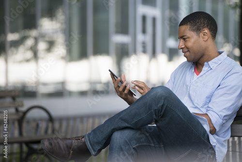 Summer In The City. People Outdoors, Keeping In Touch While On The Move. A Man Sitting On A Bench Using A Digital Tablet.