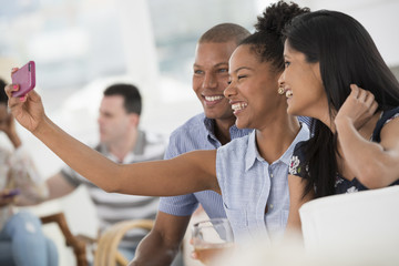 Office Event. A Woman Taking A Selfie Of The Group With A Smart Phone.