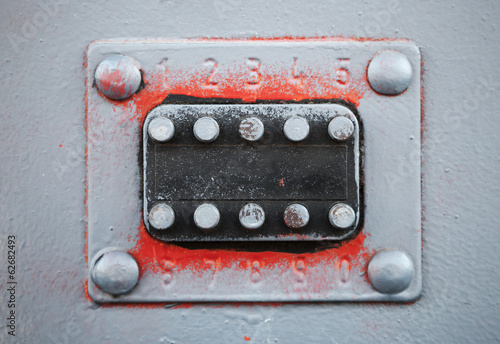 Old code lock with buttons on gray metal door