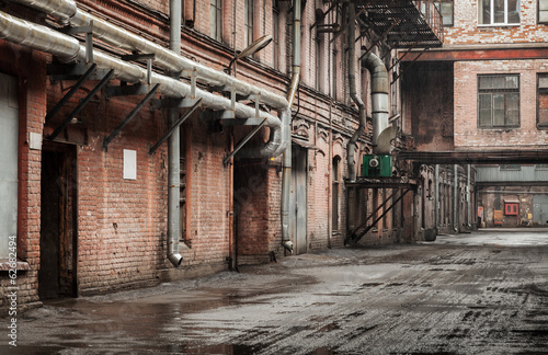 Staande foto Industrial geb. Old industrial street view with red brick facades and tubes