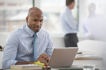 Office Life. A Businessman In A Shirt And Tie Sitting At A Desk, Using A Laptop Computer.