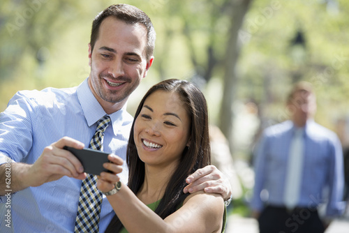 A Couple With A Smart Phone, Side By Side. A Man In The Background.