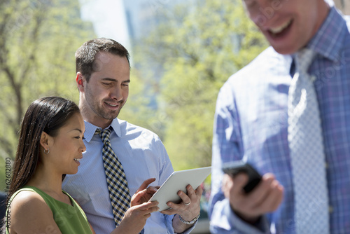 A Businesswoman And Two Businessmen Outdoors In The City. Checking Their Phones.