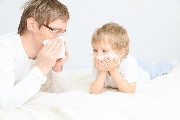 father and son wiping nose