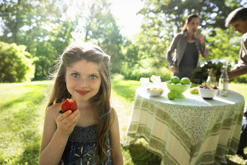 A Young Girl Holding A Large Fresh Organically Produced Strawberry Fruit. Two Adults Beside A Round Table.