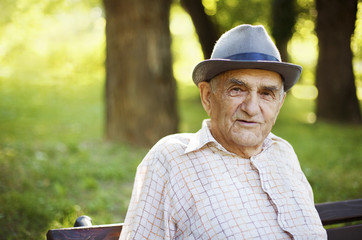 Senior man relaxing outdoors on a park early in the morning.